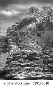 Black and white dramatic photo of Hadrian's Wall ruins on the Scottish border.