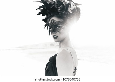 Black and white dramatic portrait of beautiful young woman in dress with black flowers and with black lace mask on face and floral crown on head. Sea background