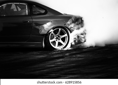 Black and white drifting car, Car wheel drifting and smoking on track.