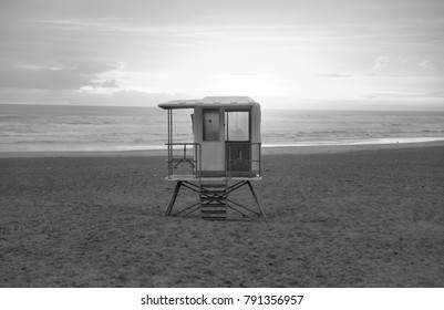 Black and white edit of a life gaurd hut overlooking the ocean shore