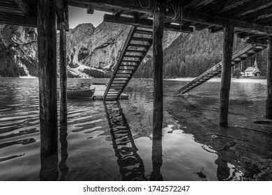 Black and white effect of rowing boats moored in an idyllic setting with mountain reflections and a small church, Braies Lake, South Tyrol, Italy. Concept: relaxation in nature, famous natural places
