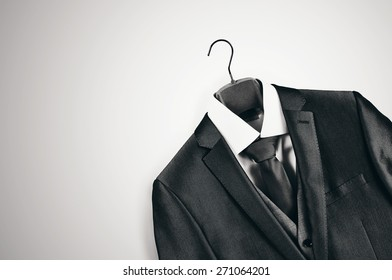 Black and white elegant mans suit on clothes hanger in bottom right corner on light grey background.