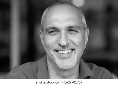 Black and white emotional portrait of a cheerful and cheerful mature European man with a bald head, smiling while looking at the girls on the street while sitting in a summer cafe. Lifestyle.