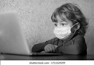Black and white emotional portrait of an enthusiastic and kind little boy in a medical mask, watching a cartoon over the Internet while quarantining self-isolation.World pandemic corona virus.Covid 19