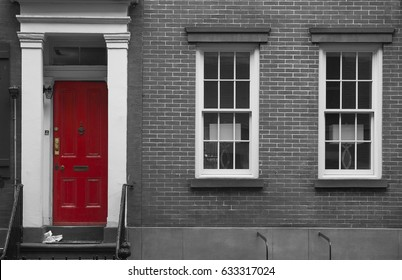 Black and white facade of a urban house with red door