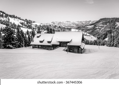 Black and white farm house in the swiss mountains during winter with snow and a mountain range in the distance