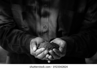 Black and white Farmer holding pile of arable soil.