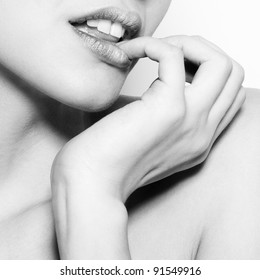 Black and white fashion abstract portrait of beautiful woman with tenderness finger and lips