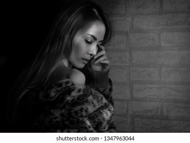 Black and white fashion closeup portrait. Young beautiful woman sexy in black clothes posing on grey background. Black hair and light makeup. Fashion, beauty. Fashion art compose photos as drawings.