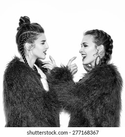 Black white fashion lifestyle portrait of two pretty best friends girls,wearing bright swag style pink fur,jewelry,having fun and make crazy funny faces.Two sisters posing on party.Hipster.Swag style.