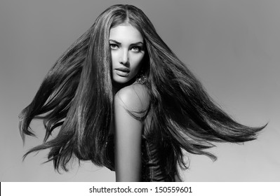 Black and White Fashion Model Girl Portrait with Long Blowing Hair. Glamour Beautiful Woman with Healthy and Beauty Hair