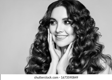Black and white fashion portrait of a beautiful young brunette with wavy hair.