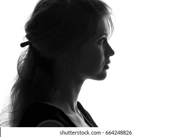 Black and white fashion portrait profile silhouette of face of a beautiful young girl with a hairstyle on her head