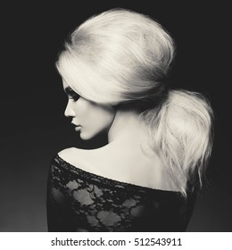 Black and white fashion studio portrait of beautiful blonde woman with elegant hairstyle on black background. Volume hairstyle. Hair tail. Hairdresser salon