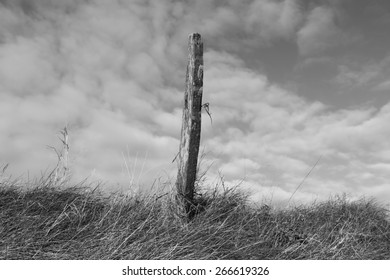 black and white fence post with dramatic sk background