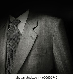 Black & White film photo of man suit detail against black background. Low key exposure to give it a sinister and dark semblance.