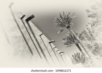A black and white filtered image of the exterior adobe wall of a traditional arabian house with strong shadows showing palm trees and drains to remove rainwater.