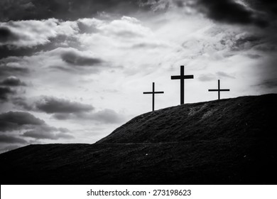 black and white filtered image of a silhouette of three crosses standing on hill with the sky lit up in the background a bright white light