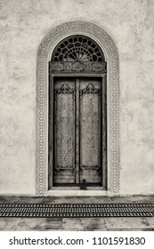 A black and white filtered view of an carved exterior door with a glass arch and a carved gypsum surround stands in front of a patterned, tiled floor in a restored traditional arabian house.