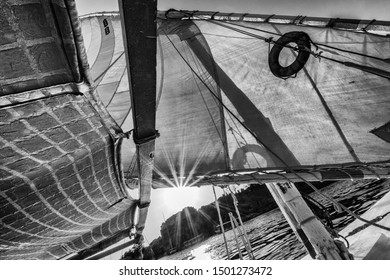 A black and white filtered view of the sun shining through rigging and the sail on an Egyptian felucca or sailing boat on the Nile at Aswan.