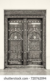 A black and white filtered view of a traditional elaborately carved Arabian house door with brass door knockers and large brass door nails.