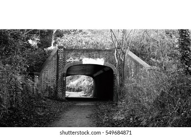 black and white of flitch way or old railway brick tunnel in the UK. England train station gate in winter season.
