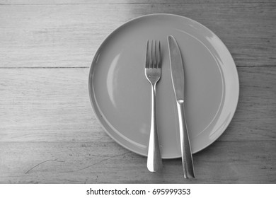 Black and white Fork and knife on an empty plate top view