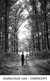 Black and white foto the newlyweds walk hand in hand along the path in the forest. Back view. Bride and groom enjoying romantic moment together on wedding day. The concept of youth, love and lifestyle