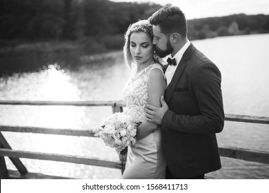 Black and white foto stylish couple of newlyweds posing on a bridge on wedding day. Handsome bearded groom admires and kisses pretty bride. Together. The concept of youth, love, fashion and lifestyle.