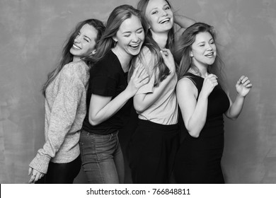 Black and white four females having hen party laughing loudly, having fun together. Best friends meeting, celebrating event or having rest during weekends.Only girls spending good time with each other