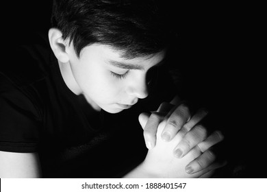 black and white frame. a child prays with folded hands
