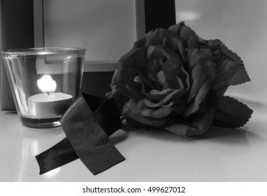 Black and white frame, flowers, black ribbons, candles, for mourning