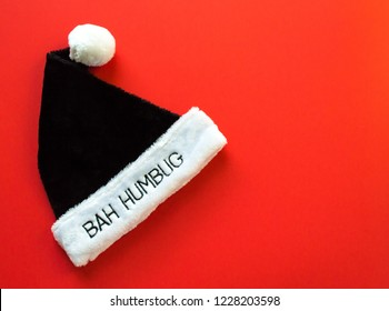 black and white fur hat saying Bah Humbug, on a red background with copy space