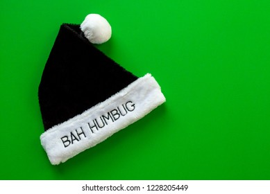 black and white fur hat saying Bah Humbug, on a green background with copy space