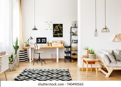 Black and white geometric carpet in multifunctional workspace with artwork on wall above desk