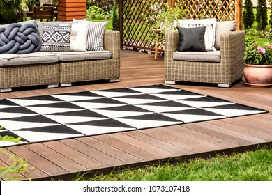 Black and white geometric carpet on wooden veranda with rattan furniture