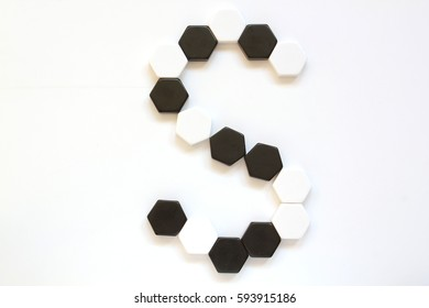 Black and white geometrical alphabet letters made of hexagonal figures laid side by side. Letter S