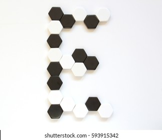 Black and white geometrical alphabet letters made of hexagonal figures laid side by side. Letter E