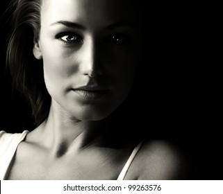 Black and white glamor woman portrait, dark beautiful face, female isolated on black background, stylish sexy look, young lady studio shot