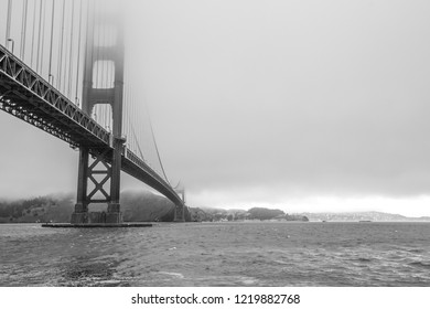 Black and white Golden Gate Bridge with fog from Fort Point, San Francisco Bay, California, United States. Symbol, icon and landmark of San Francisco. Urban BW cityscape panorama.