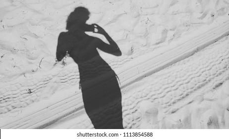 Black and white gray silhouette one woman pretty slim girl sand beach minimalism diagonal taking mobile photo