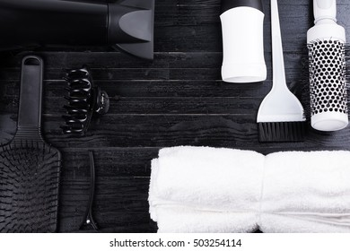 Black and white hair styling tools. Brush, dryer, clip, towel on black natural wooden table background. Copy space in the center.