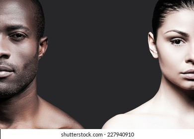 Black and white. Half faces of shirtless African man and Caucasian woman looking at camera while standing against grey background