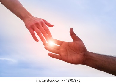 Black and white hand reaching - Handshake of different skin color hands united against racism and racial problems - Concept of human aid to migrant and refugees - Sun halo filter and dramatic light