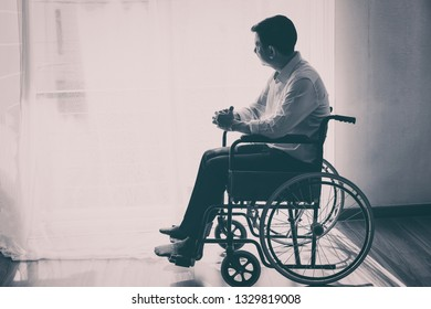 Black and white of handicapped Man sitting on wheelchair in front of a large panoramic window in hospital,He is sad and lonely.