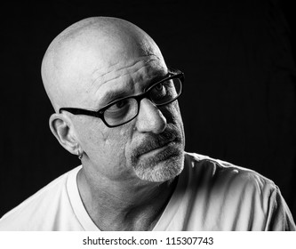 black and white head shot of a middle aged stern looking bald man with facial hair looking off to camera left on a black background