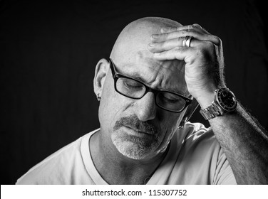 Black and white head shot of a middle aged bald man with facial hair and glasses rubbing his head with his hand on a black background