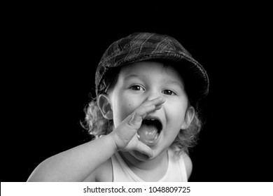 A black and white headshot of a little caucasian boy wearing a white tank top and a plaid hat shouting with his hands around his mouth. The kid is yelling and loud. There is room for text or words.