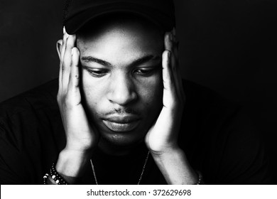 Black and White High Contrast African American Male with his hands to his face. close up head shot portrait.
