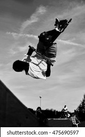 Black and white high contrast concept for background. Man making difficult scooter trick in the skatepark. Extreme boy doing high jump in rampa and rotate from the head.